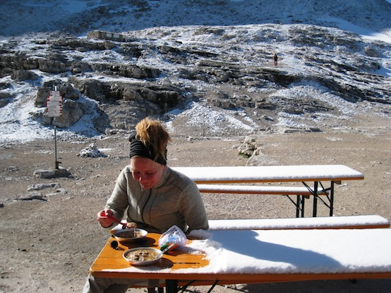 Heida eating porridge in the snow outside Rifugio Boe